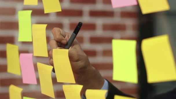 Asijský kreativní muž přilepí na skleněné desce lepkavou poznámku. Mladí profesionálští podnici píší informace, strategii, připomínku na papíře, obchodní situaci, spuštění v kanceláři v podkroví. Zpomaleně.