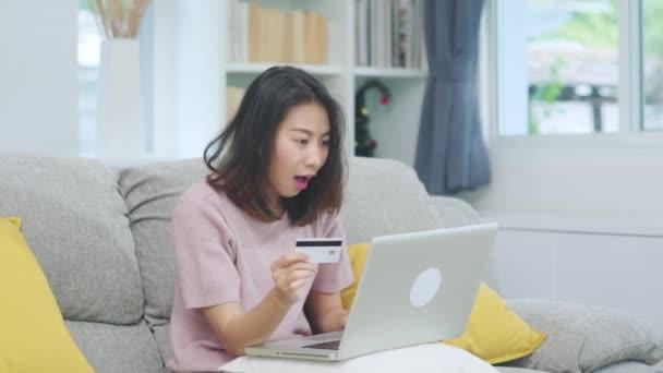 Asiatische Frau mit Laptop und Kreditkarte einkaufen E-Commerce, weibliche entspannen sich glücklich Online-Shopping sitzt auf dem Sofa im Wohnzimmer zu Hause. Lifestyle-Frauen entspannen sich zu Hause.