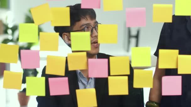 Csoport ázsiai kreatív emberek workshop és Brainstorm előtt tükör fórumon. Fiatal szakmai üzleti csapat dolgozik létre stratégia, üzleti helyzet, indítás Loft irodai koncepció. Lassított mozgás.