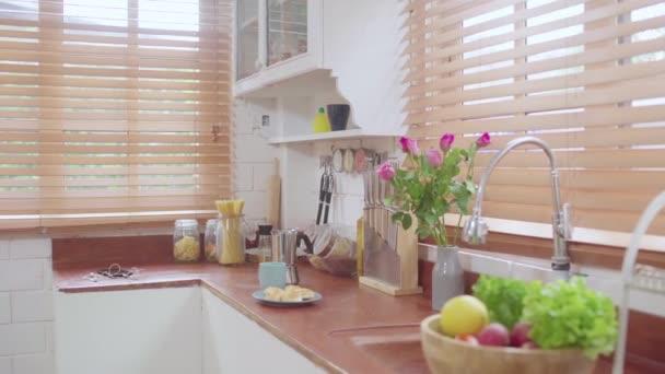 Moderní a design skandinávské kuchyně s rostlinami, příslušenstvím a košíčkem na ovoce. Slunečný a světlý prostor s bílou cihlovou stěnou.
