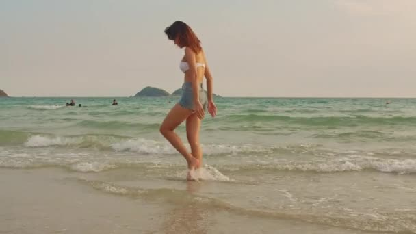 Asian woman walking on sand beach. Young happy female in bikini relax and fun walking near tropical sea when sunset while holiday, vacation, summer trip concept. Slow motion shot.