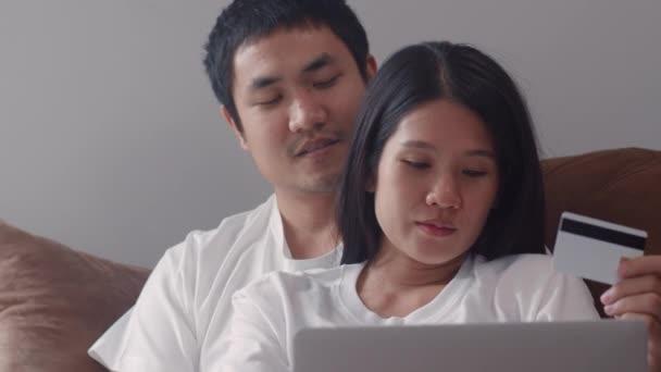 Junge asiatische Schwangere kaufen zu Hause online ein. Mama und Papa glücklich mit Laptop-Technologie und Kreditkarte Baby-Produkt kaufen, während auf dem Sofa im Wohnzimmer zu Hause Konzept.