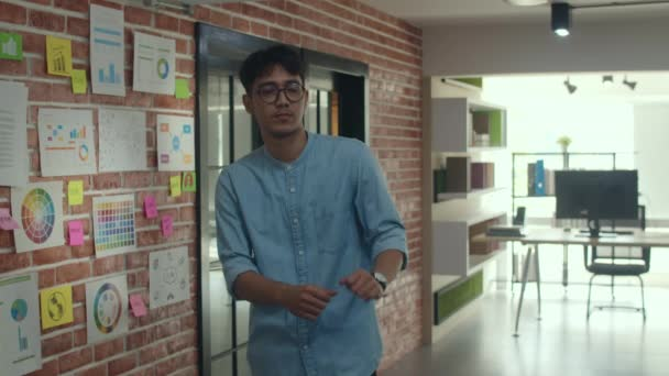 Asian creative man feeling fun and happy. Young professional business male dancing while break time, business situation, startup in Loft office concept. Slow motion.