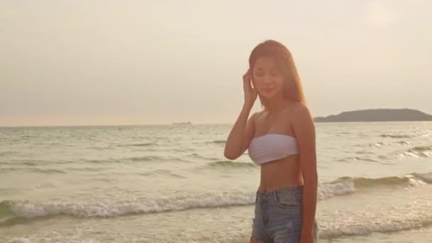 Ázsiai nő fut homokparton. Fiatal boldog nő bikini pihenni és szórakozni futni a trópusi tenger, amikor naplemente, míg ünnep, nyaralás, nyári utazás fogalmát. Lassított lövés.