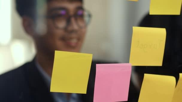 Skupina asijských kreativních mužů dílna a pracovní debata před zrcadlovou desku. Mladý profesionální obchodní tým pracuje na vytvoření strategie, obchodní situace, při startu v konceptu kanceláře v podkroví. Zpomaleně.