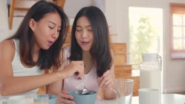 Ázsiai leszbikus LGBTQ női pár reggeli otthon, fiatal Ázsia szerető női érzés boldog italt Juice, kukoricapehely gabona-és tej tálba asztali konyhában a reggeli koncepció.