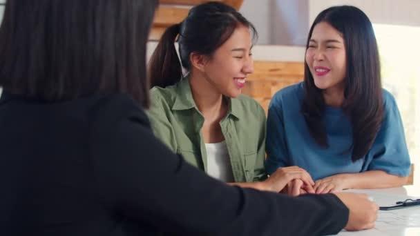 Asijská lesbička LGBTQ ženský pár podepíší Smlouvu doma, mladý pár konzultace s realitním finančním poradcem, nákup nového domu a metoda handshaking v pojetí obývacího pokoje.