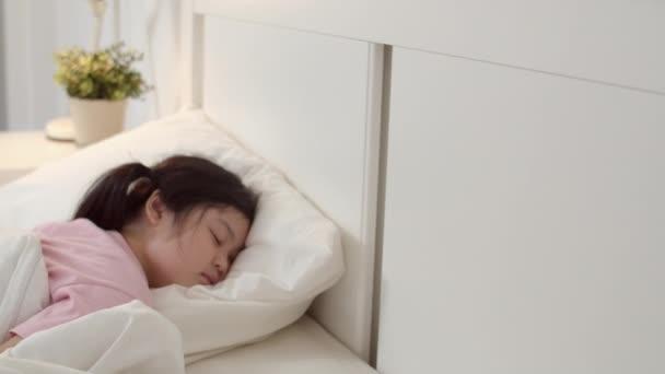Junge asiatische Mädchen schlafen zu Hause. Asiatische japanische Frau Kind entspannen Ruhe schlafen auf dem Bett, fühlen Komfort und Ruhe im Schlafzimmer zu Hause bei Nacht Konzept. Zeitlupenschuss.