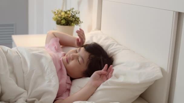 Junge asiatische Mädchen aufwachen zu Hause. Asiatische japanische Frau Kind entspannen Ruhe nach dem Schlafen die ganze Nacht liegend auf dem Bett, fühlen Komfort und Ruhe im Schlafzimmer zu Hause im MorgenKonzept. Zeitlupenschuss.