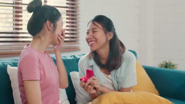 Ázsiai leszbikus LGBTQ női pár javaslatot tesz otthon, fiatal Ázsia szerető nő boldog mosolygott romantikus időt, miközben javasolja, és a házasság meglepetés kopás esküvői gyűrű a nappaliban otthon koncepció.