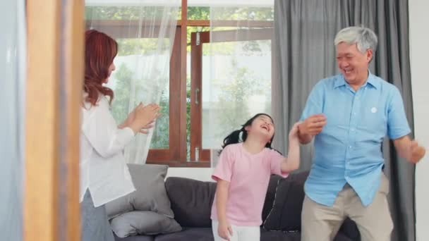 Asian grandparents and granddaughter listen to music and dance together at home. Senior Chinese, grandpa and grandma happy spend family time relax with young girl in living room concept. Slow motion.