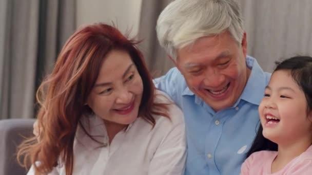 asiatische Großeltern im Gespräch mit Enkelin zu Hause. Senior Chinese, alte Generation, Großvater und Großmutter Familienzeit entspannen mit jungen Mädchen Kind auf dem Sofa im Wohnzimmer Konzept. Zeitlupe.