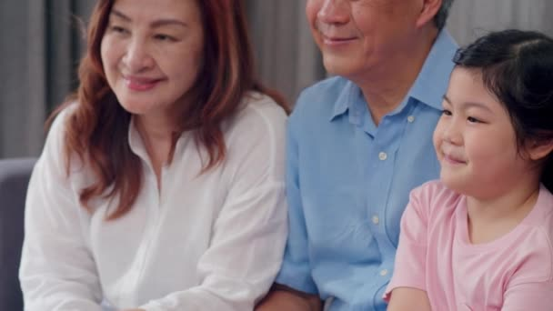 Asian grandparents talking with granddaughter at home. Senior Chinese, old generation, grandfather and grandmother family time relax with young girl kid on sofa in living room concept. Slow motion.