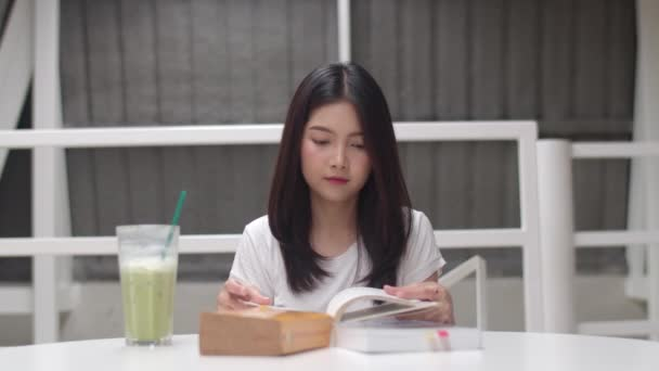 Asian student women reading books in library at university. Young undergraduate girl do homework, read textbook, study hard for knowledge and education on lecture desk at college campus. Slow motion.