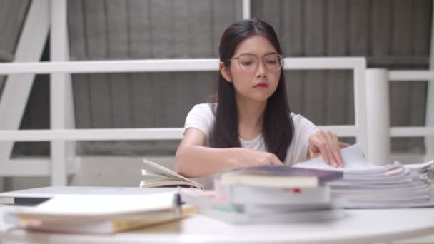 Asian student women reading books in library at university. Young undergraduate girl do homework, read textbook, study hard for knowledge and education on lecture desk at college campus concept.
