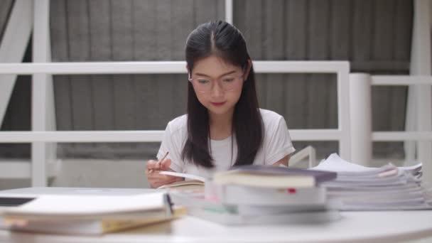Ázsiai hallgatói nők olvasatban könyvek könyvtári Egyetemen. Fiatal graduális lány nem házi feladatot, olvasni tankönyv, tanulmány keményen a tudás és az oktatás az előadóterem a főiskolán campus. Lassított mozgás.