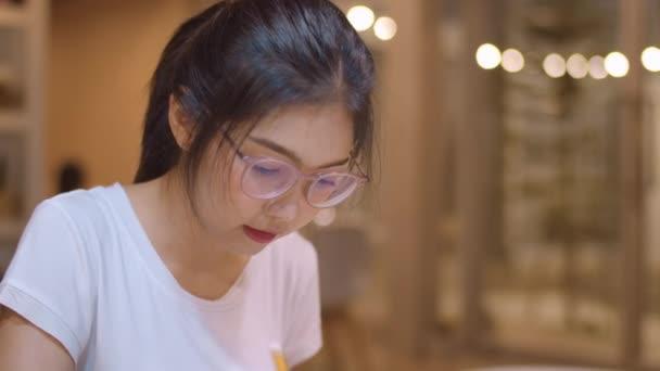 Asijské studentky čtou knihy v knihovně na univerzitě. Mladá vysokoškolka dělá domácí úkoly, čte učebnicovou knížku, pilně studuje znalosti na přednášce na universitním kampusu. Zpomaleně.
