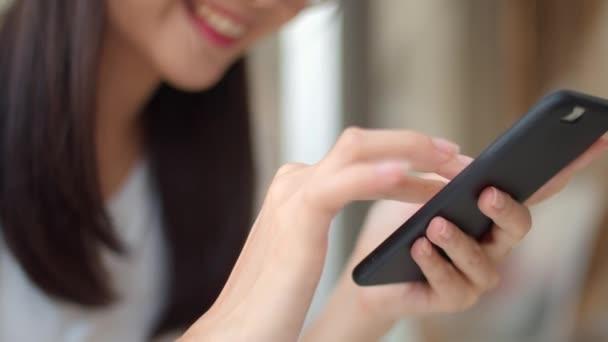 Szabadúszó ázsiai nők mobiltelefonon egy kávézóban. Fiatal Ázsia lány használ smartphone ellenőrzése szociális média Internet asztalra egy szabadtéri kávézóban az esti koncepció. Lassított mozgás