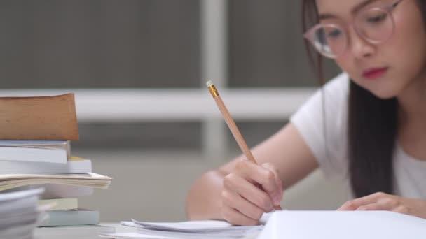 Asijské studentky čtou knihy v knihovně na univerzitě. Mladá vysokoškolská dívka dělá domácí úkoly, čte učebnicovou knížku, pilně studuje vědomosti a vzdělání na přednášce ve školní koleji. Zpomaleně.