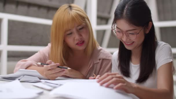 Asian student women do project in library at university. Group of young friends undergraduate girl looking books for information and knowledge on lecture desk at college campus concept. Slow motion.