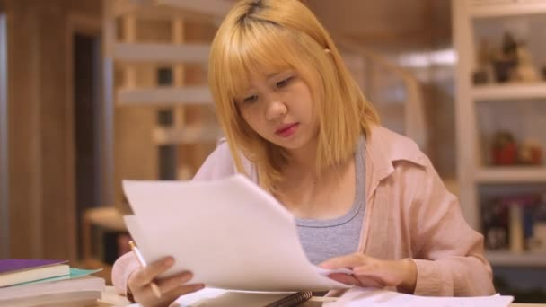 Asian student women reading books in library at university. Young undergraduate girl do homework, read textbook, study hard for knowledge on lecture desk at college campus overtime night. Slow motion.