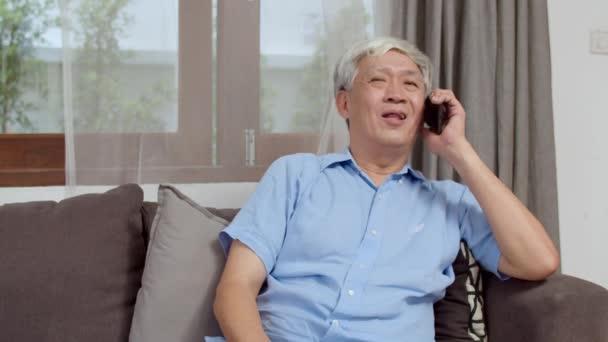 Asiatische Senioren telefonieren zu Hause. Asiatischer älterer chinesischer Mann telefoniert mit Enkelkindern der Familie, während er zu Hause auf dem Sofa im Wohnzimmer liegt.