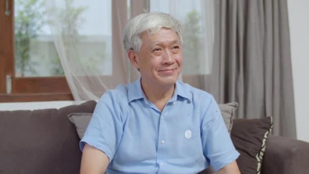Portré ázsiai kínai végzős férfi, aki boldogan mosolyog otthon. Idősebb férfi pihenni fogas mosoly nézi a kamera, miközben fekvő kanapé a nappaliban otthon a reggeli koncepció.