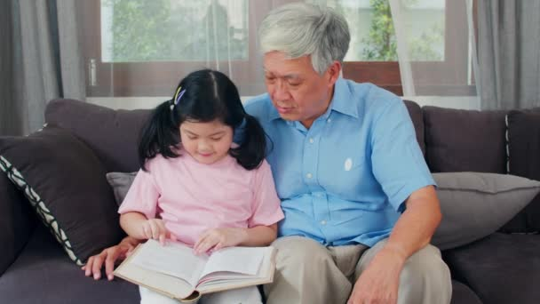 Asian grandfather relax at home. Senior Chinese, grandpa happy relax with young granddaughter girl enjoy read books and do homework together in living room concept. Slow motion shot.