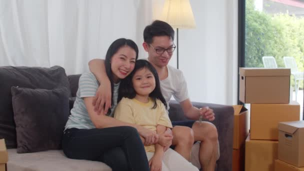 Portrait of Happy Asian young family bought new house. Japanese little preschool daughter with parents mother and father holds in hand keys sitting on sofa in living room smiling looking at camera.