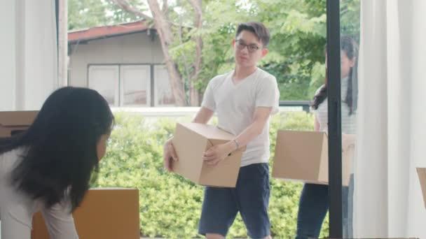 glückliche junge asiatische Familie kaufte ein neues Haus. Japanische Mama, Papa und Kind lächeln glücklich und halten Pappkartons für Umzugsobjekte in die große moderne Wohnung. neue Immobilien, Darlehen und Hypotheken.