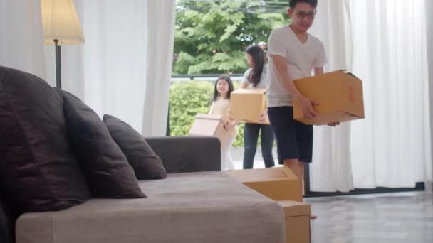 Šťastná asijská mladá rodina si koupila nový dům. Čínská máma, táta a dítě se šťastně usmívají držet lepenkové krabice na stěhování předmět držet dole ve velkém moderním domě. Nové bytové domy, úvěry a hypotéky.