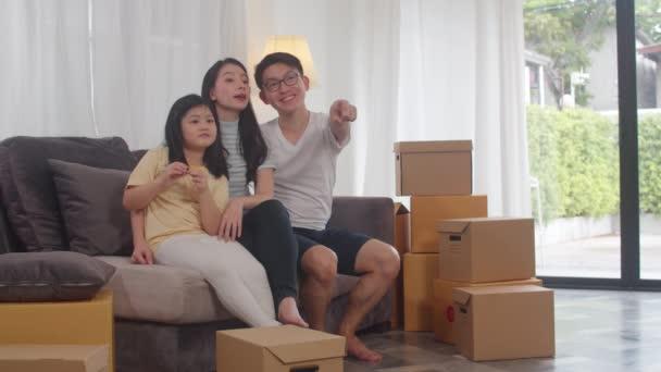 Šťastní asijští majitelé domů si koupili nový dům. Japonská maminka, táta, a dcera objímající těšit se na budoucnost v novém domově po stěhování v relokaci sedí na pohovce s krabicemi spolu.