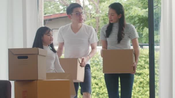 Boldog ázsiai fiatal család vett új házat. Japán anya, apa, és a gyermek mosolygó boldog hold kartondoboz mozgó tárgy besétál a nagy modern otthon. Új ingatlan-lakás, hitel és jelzálog.