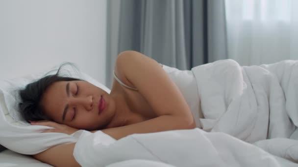 Ázsiai japán nő alszik otthon. Fiatal ázsiai lány érzés boldog pihenés feküdni az ágyon, úgy érzi, kényelmes és nyugodt a hálószobában otthon reggel. 4k állásfoglalás és lassú indítvány.