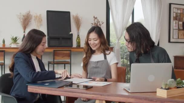 fröhliche asiatische Kleinunternehmerpaar Treffen mit Berater über Businessplan und Finanzen im Café. junger japanischer Agent erwägt, gemeinsam im Restaurant eine Versicherung abzuschließen.
