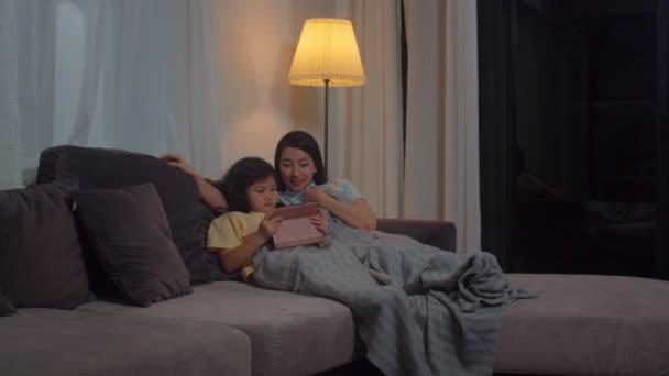 junge asiatische Familie und Tochter glücklich mit Tablette zu Hause. Koreanisch mutter entspannen mit wenig mädchen watching film liegend auf sofa vor gehen schlafen im wohnzimmer bei haus in nacht.