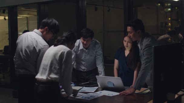 Millennial Asia businessmen and businesswomen meeting brainstorming ideas about new paperwork project colleagues working together planning success strategy enjoy teamwork in small modern night office.