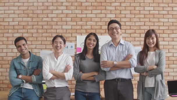 Portrait of successful businessman and businesswoman smart casual wear looking at camera and smile, arms crossed in creative office workplace. Diverse Asia male and female stand together at startup.