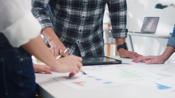 Millennial Asia Geschäftsleute treffen sich zu Brainstorming-Ideen über neue Papierkram-Projektkollegen, die gemeinsam eine Erfolgsstrategie planen, genießen Teamarbeit in kleinen modernen Nachtbüros.