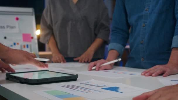 Millennial Asia Geschäftsleute und Geschäftsfrauen, die Brainstorming-Ideen über neue Papierkram-Projektkollegen treffen, die gemeinsam eine Erfolgsstrategie planen, genießen Teamarbeit in kleinen modernen Nachtbüros.