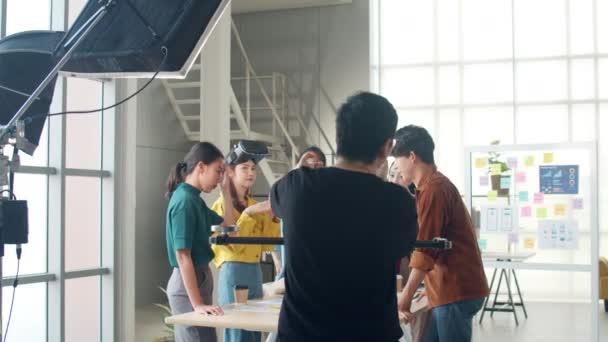 Hinter den Kulissen der Videoproduktion Team Shooting-Gruppe von Asien junge kreative Menschen diskutieren Business Brainstorming Treffen Ideen mobile Anwendung Software-Design-Projekt im Büro.