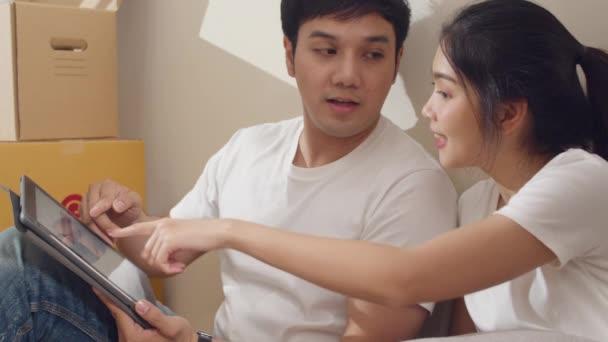 Šťastný asijský mladý pár si koupil nový dům. Korejská rodina používá digitální tablet diskutovat o interiérových návrzích renovace sedí na podlaze ve velkém moderním domě. Nové bytové domy, úvěry a hypotéky.