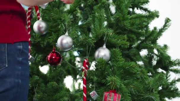 Asian female decorated with ornament on Christmas tree at Christmas and New Year festival at home. Xmas celebration event preparation or winter holidays festival indoor party concept. Close up shot.