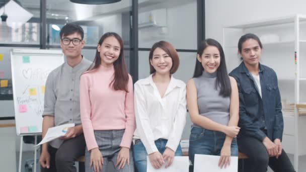 Group of Asia young creative people in smart casual wear smiling and thumbs up in creative office workplace. Diverse Asian male and female stand together at startup. Coworker teamwork concept.