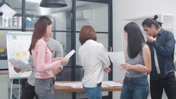 Skupina asijských mladých kreativních lidí v elegantním neformálním oblečení při pohledu do kamery a úsměvu na kreativním kancelářském pracovišti. Různí asijští muži a ženy stojí při startu společně. Koncept týmové práce spolupracovníků.