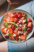 Young man holding fresh tasty summer salad with fruits, berries and vegetables. View from above, closeup