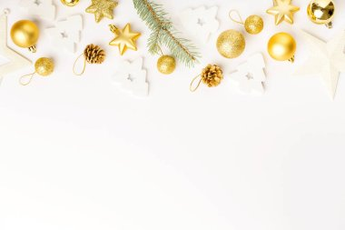 Flat Lay of Christmas golden decorative baubles and fir twig isolated on white