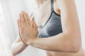 Fotografia mani di donna in abiti sportivi che meditating nella luce del giorno