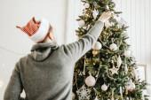 Karácsonyi kalapos férfi díszíti a karácsonyfát a házban. Életstílus. Karácsonyi otthon koncepció.