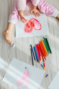 Cute little girl drawing red heart at home